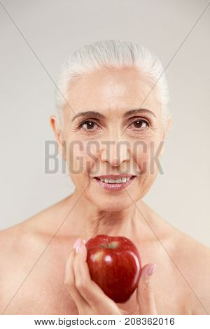 Beauty portrait of an attractive half naked elderly woman holding apple and looking at camera isolated over white background