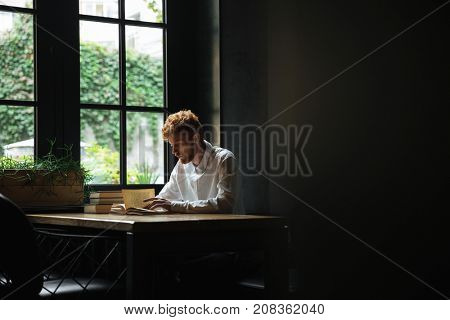 Photo of young readhead bearded man reading a book in cafeteria