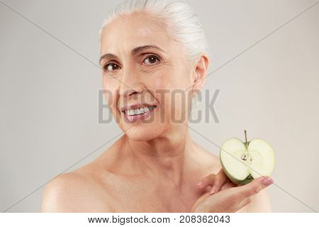 Beauty portrait of a happy half naked elderly woman holding sliced green apple and looking at camera isolated over white background
