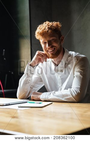 Young cheerful readhead bearded man in white shirt, sitting on his workplace, looking at camera