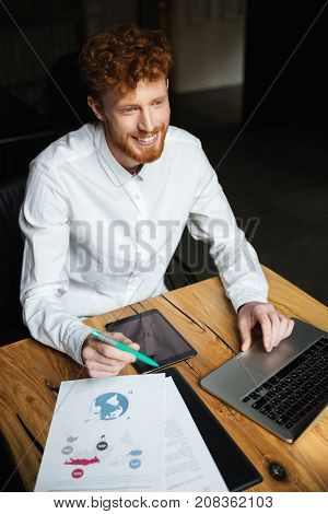 Close-up portrait of young cheerful readhead curly business man in white shirt working on laptop, looking aside