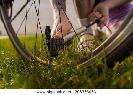 Man Pumping Bicycle Wheel