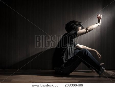 depressed man sitting head in hands,sport light on the man