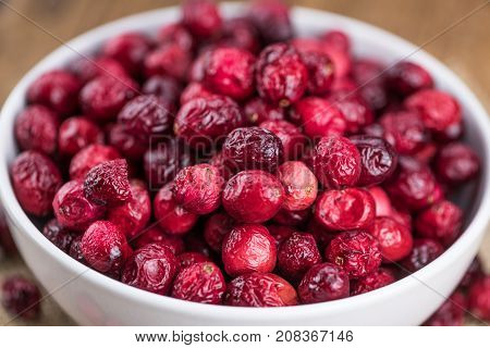 Some Fresh Dried Cranberries On Wooden Background (selective Focus; Close-up Shot)