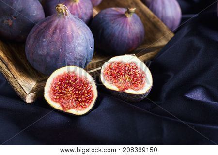 Ripe fig halves and whole figs in wooden bowl on purple backdrop