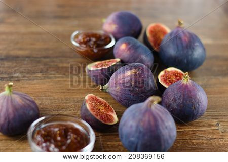 Ripe blue and purple figs both whole and cut in half randomly spilled on dark wood table among glass bowls of fig jam