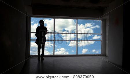 Back or rare view of women silhouette beside the big window and sky with cloud backgroundfreedom concept