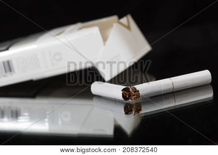 Broken cigar and empty box of cigarettes on the black