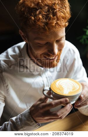 Close-up portrait of handsome young readhead beraded guy holding coffee cup