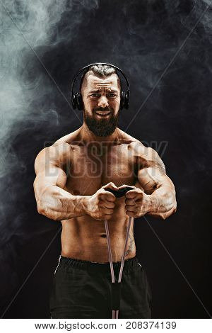 Fitness man in headphones exercising with stretching band in studio.