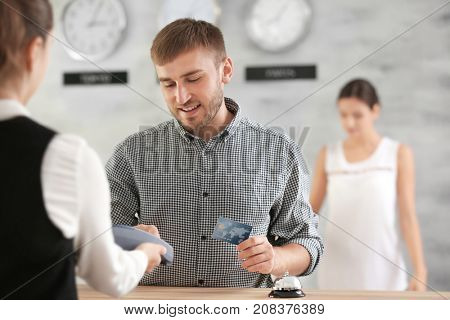 Young man paying for hotel room at reception