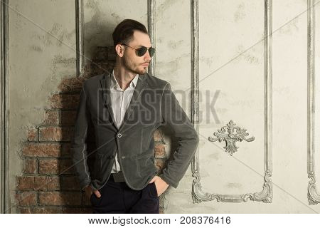 young handsome man with unshaven on his face wearing black glasses with a pensive look in a suit against the background of a light wall