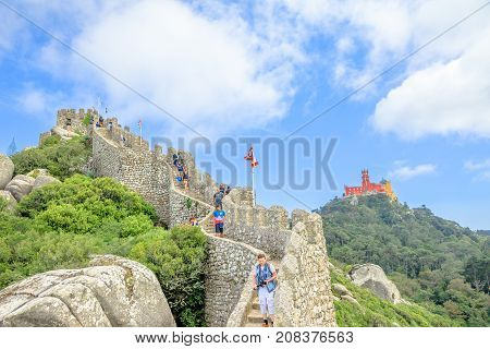 Sintra, Portugal - August 7, 2017: one of towers of panoramic Castle of the Moors with coloful Pena Palace in the distance. People visit one of the two most popular Sintra landmarks.