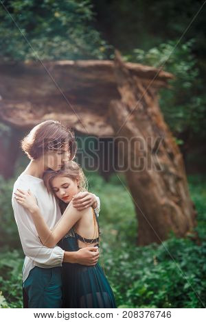 Young couple of elves in love in magical forest agaist the broken tree outdoor on nature. Fairy tale love, relationship and magik people concept. Man ambracing woman