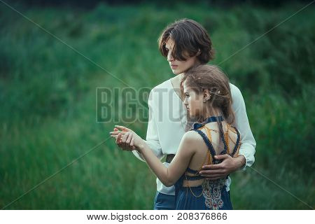 Young couple of elves in love standing in magical forest outdoor on nature. Fairy tale love, relationship and magik people concept. Man holding woman by hands and ambracing and looking away
