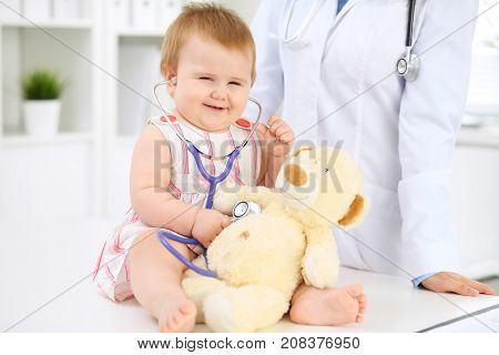 Happy cute baby at health exam at doctor's office. Toddler girl is sitting and keeping stethoscope and teddy bear.