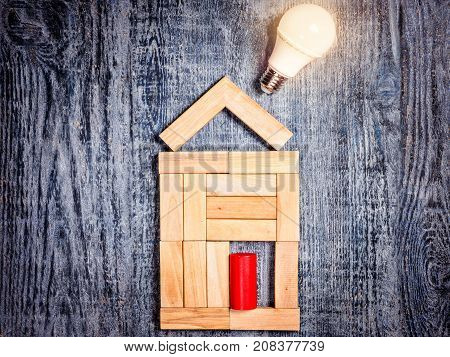 Home improvement concept. Idea for construction, energy saving, economic electric lighting of house. Form of house above tree on dark wooden background and  LED bulb instead of exhaust pipe, flue. Imitation of heating copper or boiler and air conditioner.