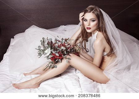 Body Of Young, Beautiful And Sexy Bride In Erotic White Lingerie, Sitting In Bed And Holding Flowers