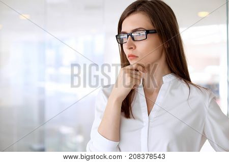 Modern business woman looks concerned while standing in the office.