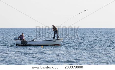 Ulcinj riviera - October 1 2017: Two fishermen chase fish on the net with cargo on a rope from a boat in the blue sea on the Great Montenegrin beach Ulcinj Riviera Montenegro