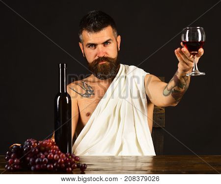 Man With Beard Holds Glass Of Wine On Brown Background.