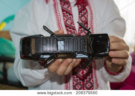 boy in his hands holds a toy car black