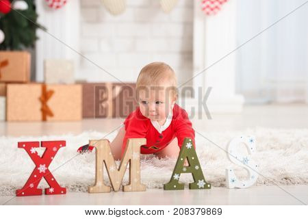 Cute baby in Santa Claus costume and word XMAS on floor at home