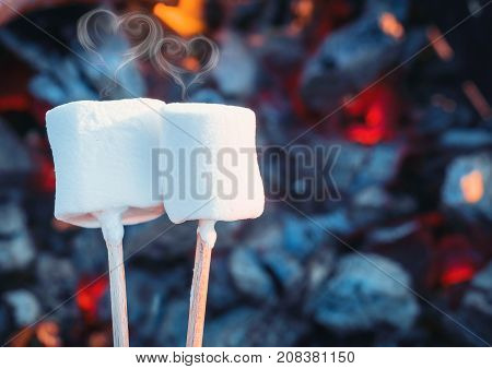 Two white sweet marshmallows roasting over fire flames. Smoke in form of hearts. Marshmallow on skewers roasted on charcoals. Sweet love concept