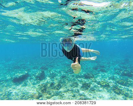 Woman snorkeling in clear sea water. Snorkel shows thumb in full face mask. Beautiful girl swims in sea. Underwater photo of oceanic landscape. Seaside adventure. Summer water sport in tropic sea
