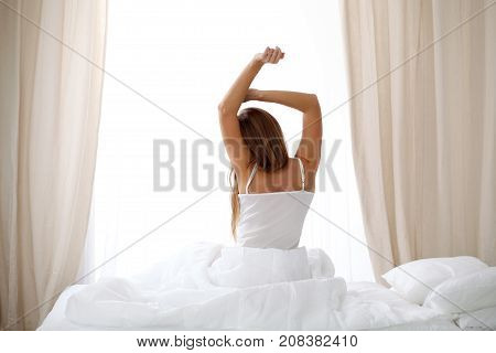 Woman stretching in bed after wake up, back view, entering a day happy and relaxed after good night sleep. Sweet dreams, good morning, new day, weekend, holidays concept.