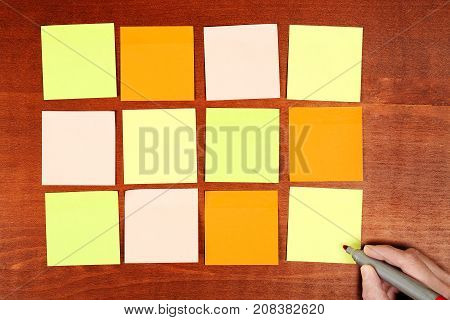 hand with marker writing on blank adhesive notes