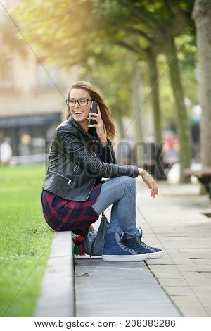 Young woman sitting in park, talking on phone