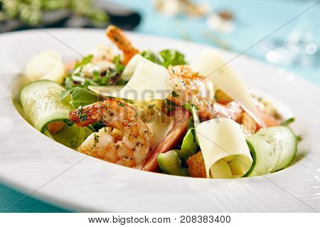 Menu of gastronomic restaurant. Caesar salad with shrimps and fresh vegetables sprinkled with herbs and seasonings