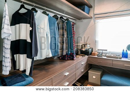 Room with wooden shelves and dresses hanging under the rack there are garment baskets with drawers.
