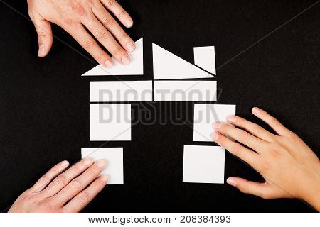 family of three forming a house with paper pieces