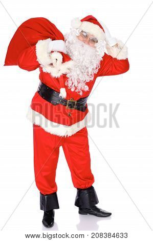 Santa Claus standing with his sack full of presents, isolated on white background. Full length portrait.