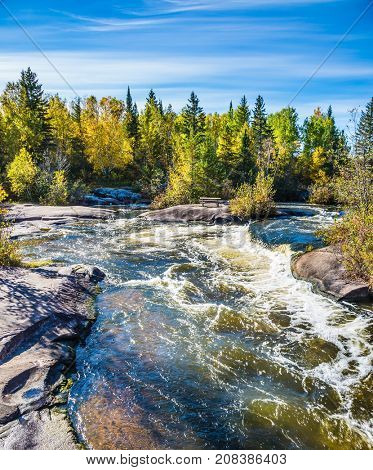 Warm autumn day. Foam water rapids on the smooth stones of the Winnipeg River. Old Pinawa Dam Provincial Heritage Park. The concept of ecological and adventure tourism