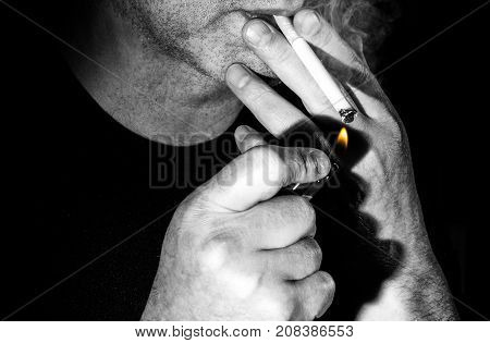 a man lights a cigarette on a black background the harm of smoking on a back background
