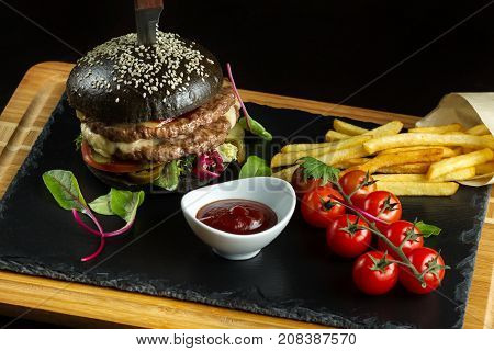 Black double hamburger made from beef, with jalapeno pepper. Next a sprig of cherry tomatoes. Overall plan.