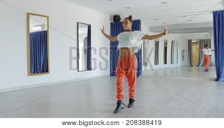 Young concentrated woman in sportive clothing dancing with hands apart while dancing in middle of spacious studio looking forward.