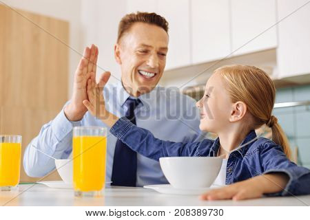 High five. Positive delighted nice girl sitting at the table and looking at her father while giving him high five