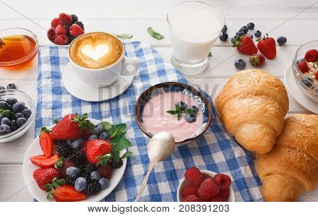 Rich continental breakfast. French crusty croissants, muesli, greek yogurt, glass of fresh milk, cup of hot black coffee and lots of sweet berries for tasty morning meals. Delicious start of the day