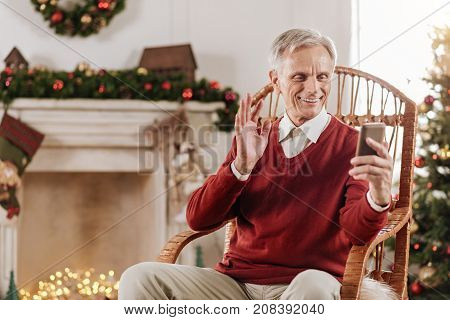 Online conversation. Retired man expressing positivity and wrinkling forehead while looking at his telephone