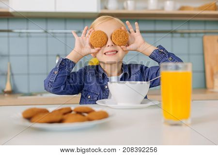 Look at me. Happy nice positive girl holding cookies and putting them to her eyes while being in a playful mood