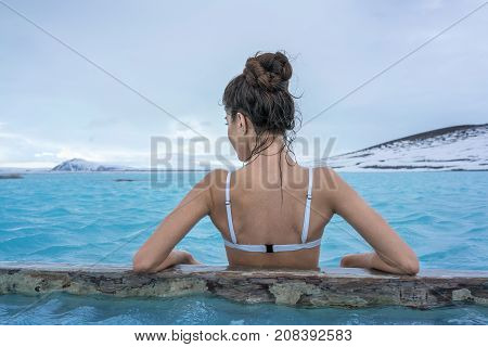 Cute girl in a white swimsuit leans on a wooden crossbeam in the geothermal pool on the background of snow mountains and cloudy sky outdoors in Iceland. Shoot from the back. Closeup. Horizontal.