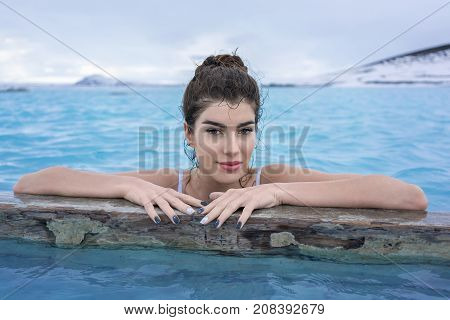 Pretty girl in a white swimsuit holds her hands on a wooden crossbeam in the geothermal pool on the background of snow mountains and cloudy sky outdoors in Iceland. She looks into camera with a smile.