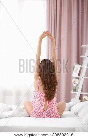 Young woman stretching on bed in morning