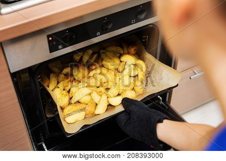 woman removing prepared potatoes tray out of oven