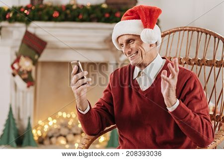 Christmas mood. Happy man keeping smile on his face and raising left hand while having online conversation