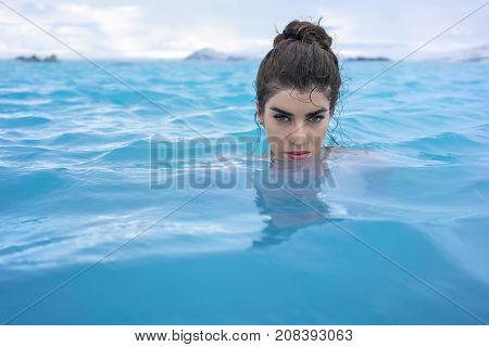 Attractive girl relaxing in the geothermal pool on the background of snow mountains and cloudy sky outdoors in Iceland. She looks into the camera. Closeup. Horizontal.